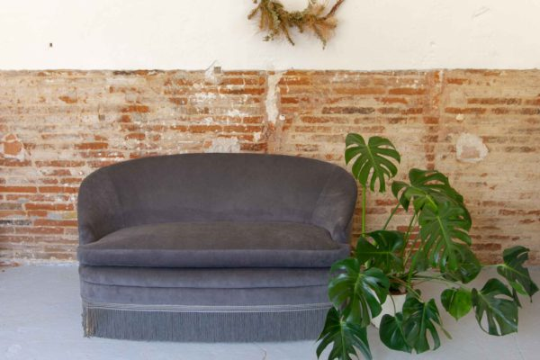 Sofá curvo de los años 60-70 tapizado en terciopelo gris con fleco en el bajo