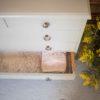 Visión cenital cómoda de madera color piedra, con cinco cajones y tiradores de latón
